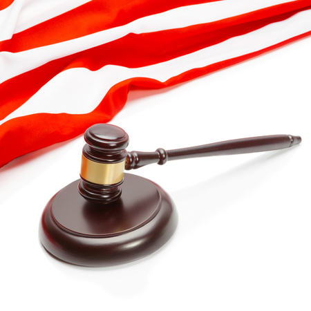 Close up shot of a wooden judge gavel near flag of Unites States of America