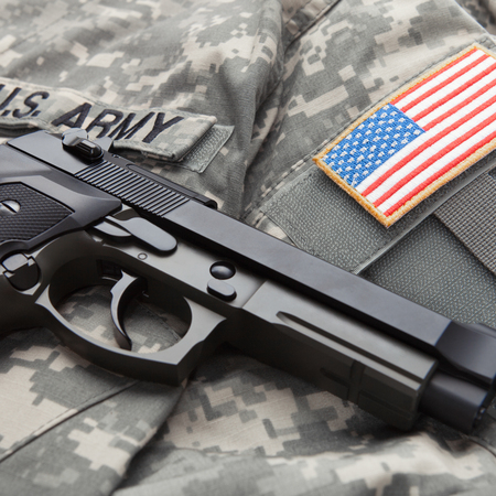 solders: Close up studio shot of a handgun over US solders uniform with USA flag shoulder patch on it Stock Photo