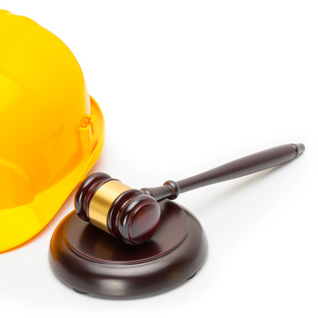 Close up shot of a wooden judge gavel near yellow protective helmet