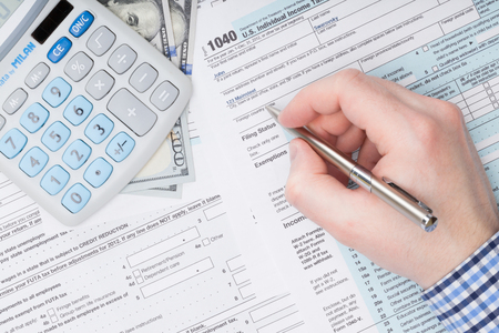 taxable income: A man filling out USA Tax 1040 Form with calculator neat it