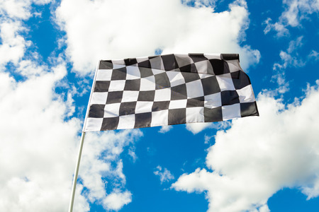 completion: Checkered flag on flagpole waving in the wind with clouds on background