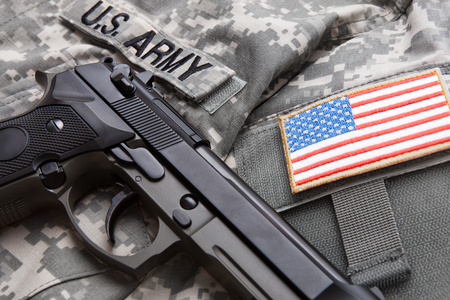 solders: Close up studio shot of handgun over USA solders uniform and USA flag shoulder patch on it Stock Photo