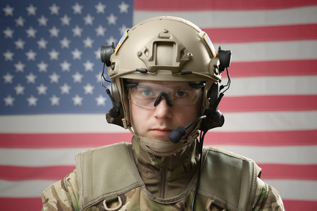 Military man wearing helmet with USA flag on background Stock Photo