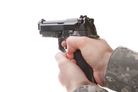 semi automatic: Man in military uniform holding hand gun and ready to use it