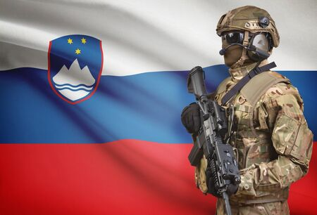Soldier in helmet holding machine gun with national flag on background - Slovenia