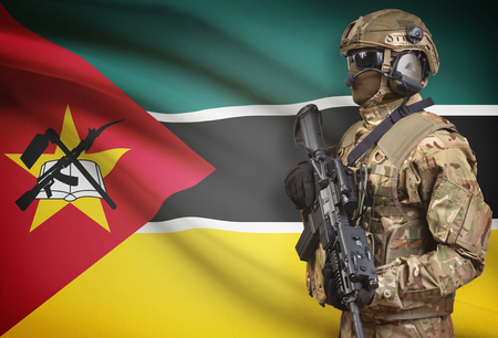 Soldier in helmet holding machine gun with national flag on background - Mozambique