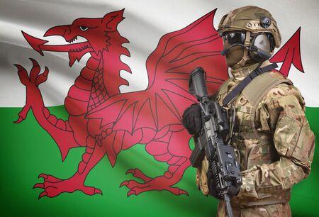 Soldato in mitragliatrice della tenuta del casco con la bandiera nazionale su fondo - Galles Archivio Fotografico