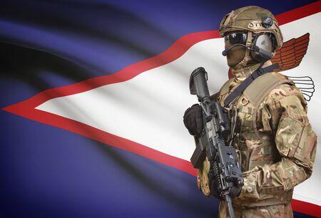 american hero: Soldier in helmet holding machine gun with national flag on background - American Samoa