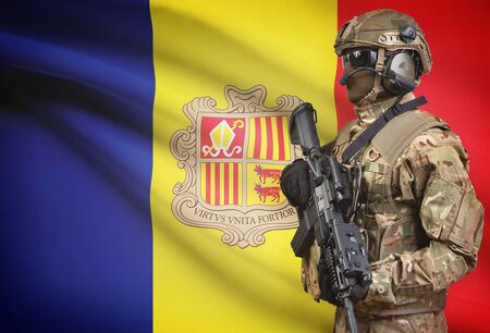 Soldier in helmet holding machine gun with national flag on background - Andorra Stock Photo