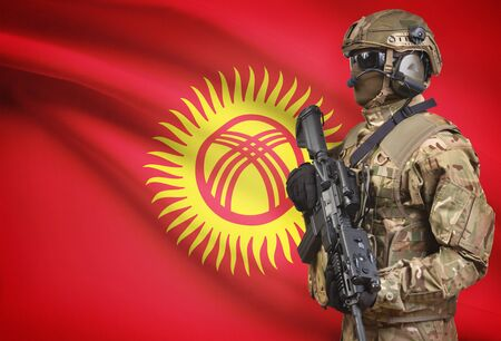 kyrgyzstan: Soldier in helmet holding machine gun with national flag on background - Kyrgyzstan Foto de archivo