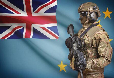 Soldier in helmet holding machine gun with national flag on background - Tuvalu