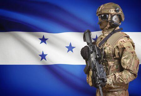 Soldier in helmet holding machine gun with national flag on background - Honduras