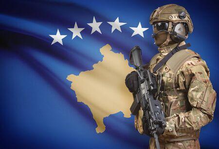 troop: Soldier in helmet holding machine gun with national flag on background - Kosovo Stock Photo
