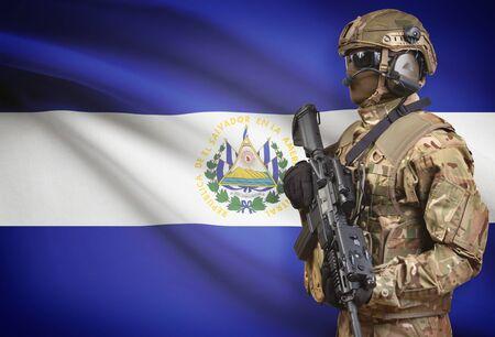 bandera de el salvador: Soldier in helmet holding machine gun with national flag on background - El Salvador Foto de archivo