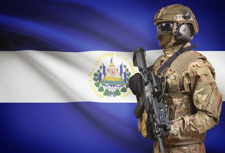 Soldier in helmet holding machine gun with national flag on background - El Salvador Stock Photo