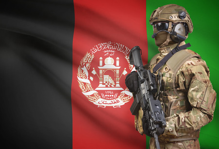Soldier in helmet holding machine gun with national flag on background - Afghanistan Stock Photo