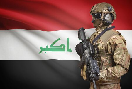 Soldier in helmet holding machine gun with national flag on background - Iraq