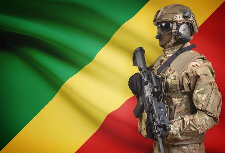 Soldier in helmet holding machine gun with national flag on background - Congo-Brazzaville Stock Photo