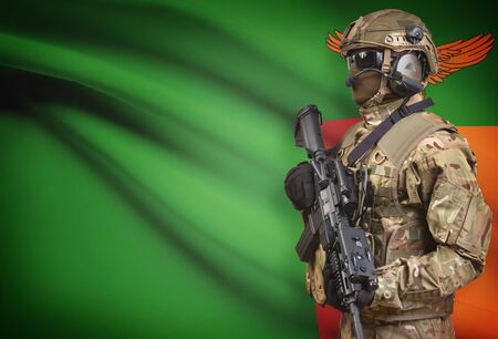 Soldier in helmet holding machine gun with national flag on background - Zambia