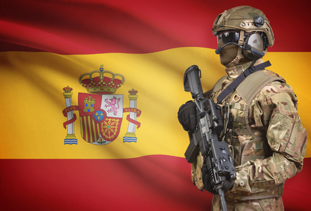 Soldier in helmet holding machine gun with national flag on background - Spain