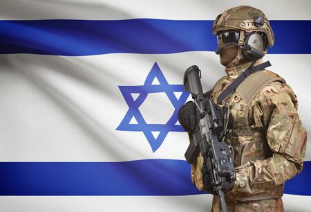 Soldier in helmet holding machine gun with national flag on background - Israel