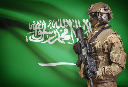 Soldier in helmet holding machine gun with national flag on background - Saudi Arabia