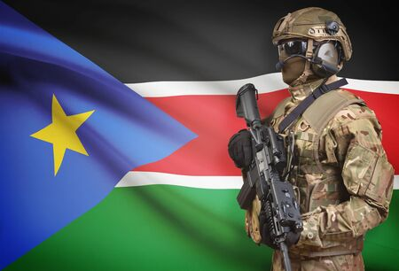troop: Soldier in helmet holding machine gun with national flag on background - South Sudan