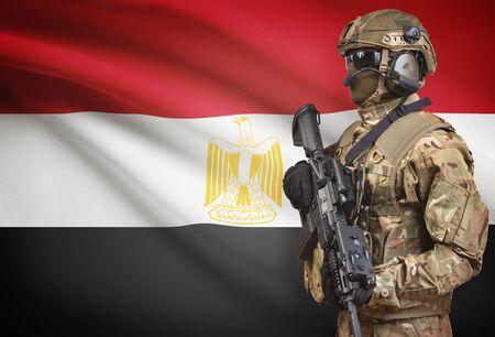 bandera de egipto: Soldier in helmet holding machine gun with national flag on background - Egypt