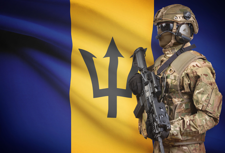 Soldier in helmet holding machine gun with national flag on background - Barbados Stock Photo