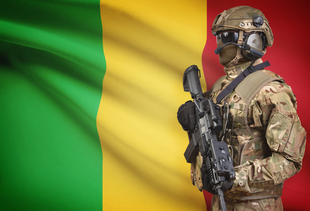 Soldier in helmet holding machine gun with national flag on background - Mali