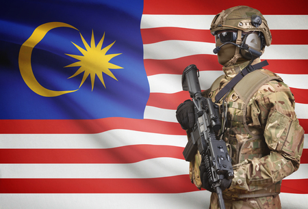 Soldier in helmet holding machine gun with national flag on background - Malaysia