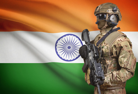 Soldier in helmet holding machine gun with national flag on background - India Stock Photo