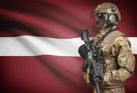 Soldier in helmet holding machine gun with national flag on background - Latvia