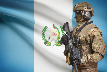 bandera de guatemala: Soldier in helmet holding machine gun with national flag on background - Guatemala