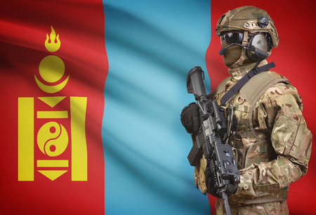 Soldier in helmet holding machine gun with national flag on background - Mongolia