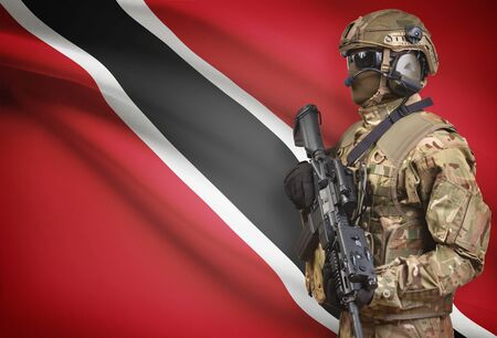 Soldier in helmet holding machine gun with national flag on background - Trinidad and Tobago