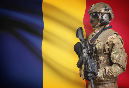 Soldier in helmet holding machine gun with national flag on background - Chad