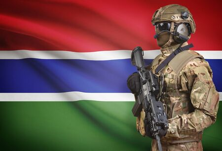 Soldier in helmet holding machine gun with national flag on background - Gambia Stock Photo