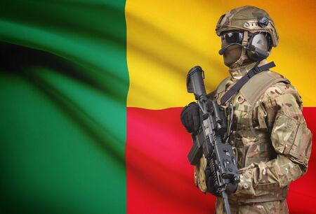 Soldier in helmet holding machine gun with national flag on background - Benin Stock Photo