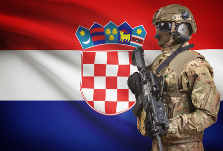 bandera croacia: Soldier in helmet holding machine gun with national flag on background - Croatia