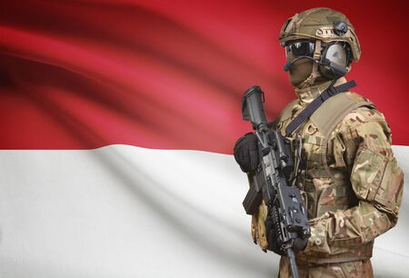 Soldier in helmet holding machine gun with national flag on background - Monaco Stock Photo