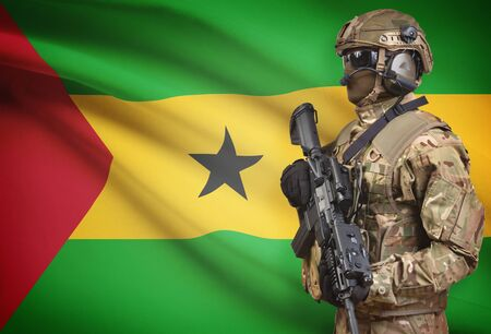 principe: Soldier in helmet holding machine gun with national flag on background - Sao Tome and Principe Foto de archivo