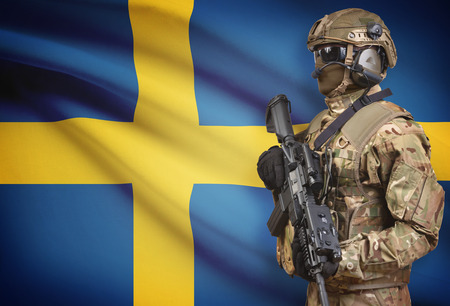 Soldier in helmet holding machine gun with national flag on background - Sweden Stock Photo
