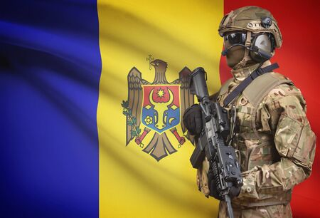 Soldier in helmet holding machine gun with national flag on background - Moldova