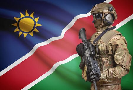 Soldier in helmet holding machine gun with national flag on background - Namibia