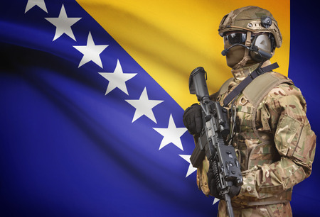 Soldier in helmet holding machine gun with national flag on background - Bosnia and Herzegovina Stock Photo