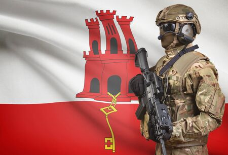 Soldier in helmet holding machine gun with national flag on background - Gibraltar