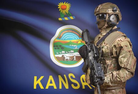 Soldier in helmet holding machine gun with USA state flag on background - Kansas Stock Photo