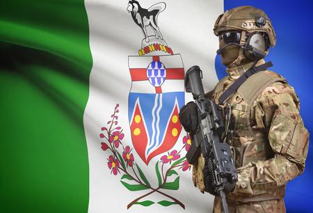 yukon territory: Soldier in helmet holding machine gun with Canadian province flag on background - Yukon Stock Photo