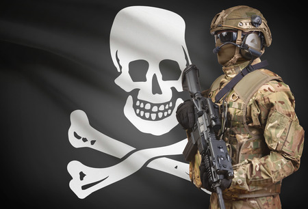 Soldier in helmet with  machine gun and flag on background - Jolly Roger
